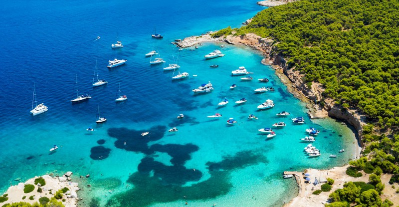 Der beliebte Strand auf der kleinen Insel Moni gegenüber von Perdika bei Ägina mit türkisem Meer und zahlreichen Segelbooten, Griechenland
