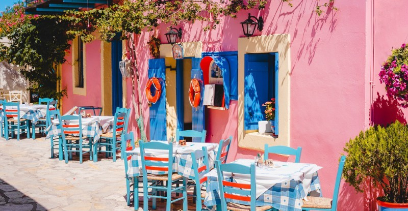 Traditional greek vivid lilac colored tavern on the narrow Mediterranean street on hot summer day