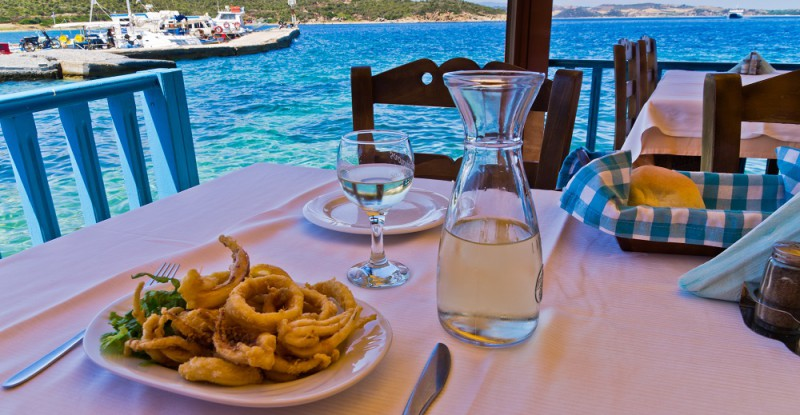 Fried squid and white wine in a shade of a typical greek taverna in a harbour at Amoulani island, Greece